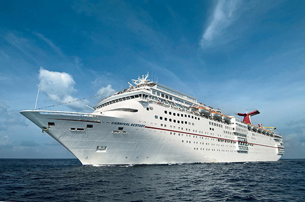 Carnival Cruise Lines' 855-foot-long Carnival Ecstasy cruises off Cozumel, Mexico. The 70,000-ton, 2,052-passenger liner is part of the line's popular Fantasy-class, one of the most successful series of cruise ships ever introduced. Photo by Andy Newman/Carnival Cruise Lines.